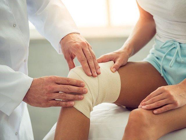 Foto van dame met gevoelloosheid in knie.Wordt behandeld door een gezondheidsdeskundige.